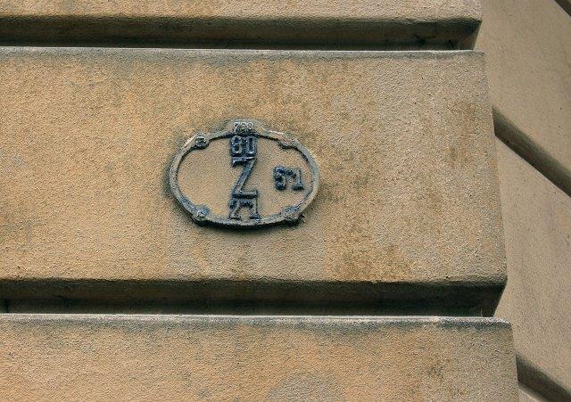 """Табличка з літерою """"H"""", що вказує на гідрант (H) на будинку у Львові"""