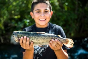 Isiah Jeantete, of Taos, shows off a fish he caught near the Red River Fish Hatchery