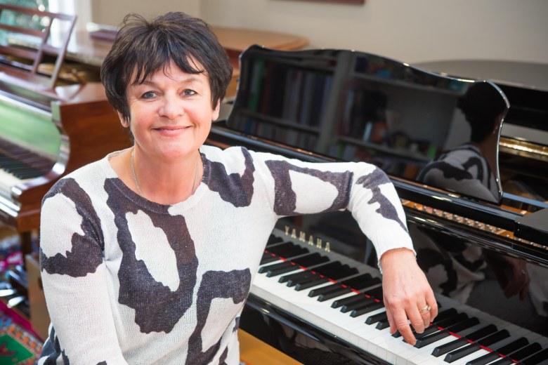 Elena Roujnikova piano teacher sitting at Yamaha piano