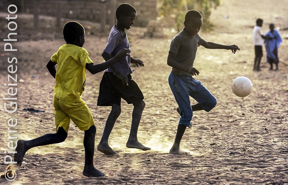 Jeunes garcons jouant au foot pieds nus , fin de journee, poussieres