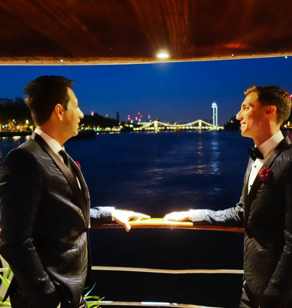 Antoine and Martin look out over the Thames at night from the MV Edwardian, London
