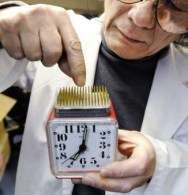 """Kenji Kawakami, inventor and founder of the International Chindogu Society demonstrates an alarm clock with the """"snooze"""" button located in the middle of a bed of sharp pins designed to help keep user awake in Tokyo on June 3, 2009. The word """"Chindogu"""" translates as """"weird tools"""" and Kawakami has invented hundreds of these often bizzare and absurd items. AFP PHOTO/YOSHIKAZU TSUNO (Photo credit should read YOSHIKAZU TSUNO/AFP/Getty Images)"""