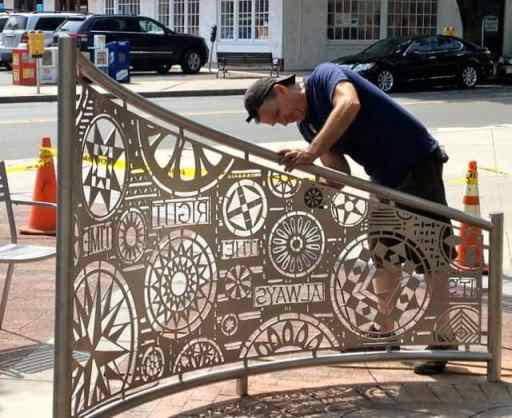 Tom Nussbaum polishes the newly installed stainless steel gates on Hinds Plaza Wednesday.