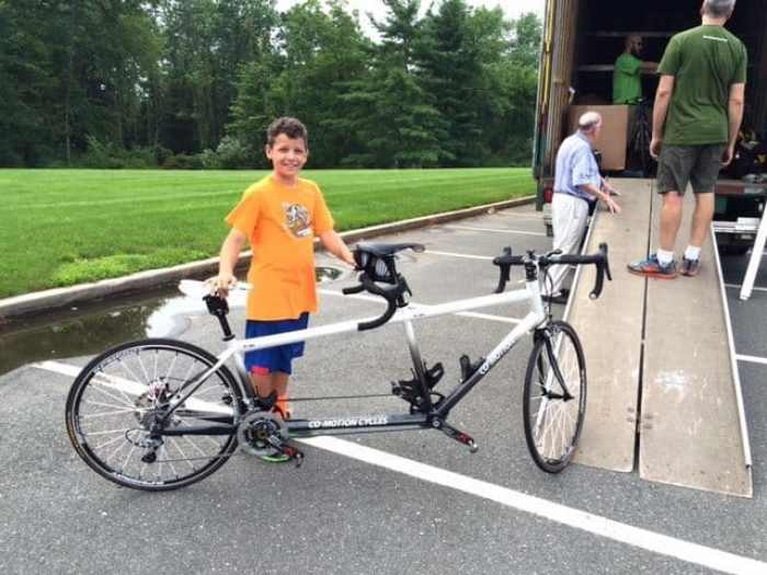Henry Garnich, whose parents own Knapp's Cyclery, helps load a tandem bike on a truck Thursday night at Timberlane Middle School.