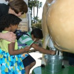 Secretary Ross joins children experiencing Buttercup the robotic milking cow.