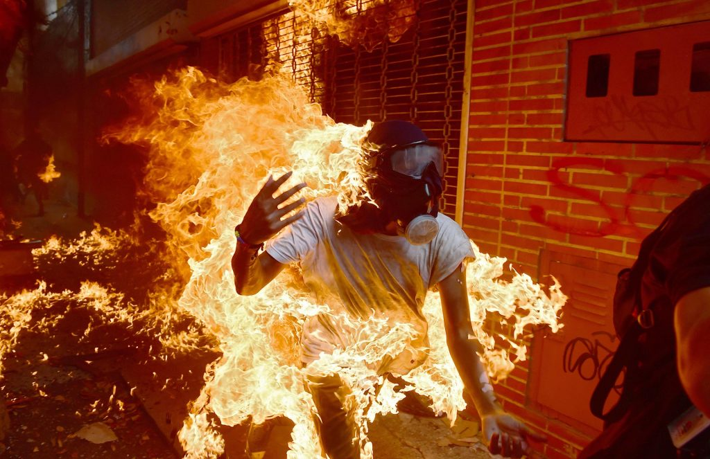 A demonstrator catches fire during clashes with riot police within a protest against Venezuelan President Nicolas Maduro, in Caracas on May 3, 2017. Venezuela's angry opposition rallied Wednesday vowing huge street protests against President Nicolas Maduro's plan to rewrite the constitution and accusing him of dodging elections to cling to power despite deadly unrest. / AFP PHOTO / RONALDO SCHEMIDT