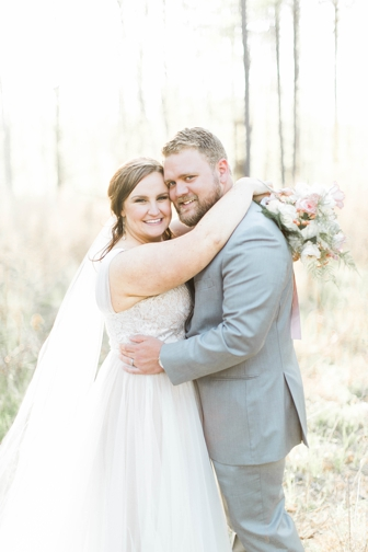 plus size bride and groom holding bouquet in a field