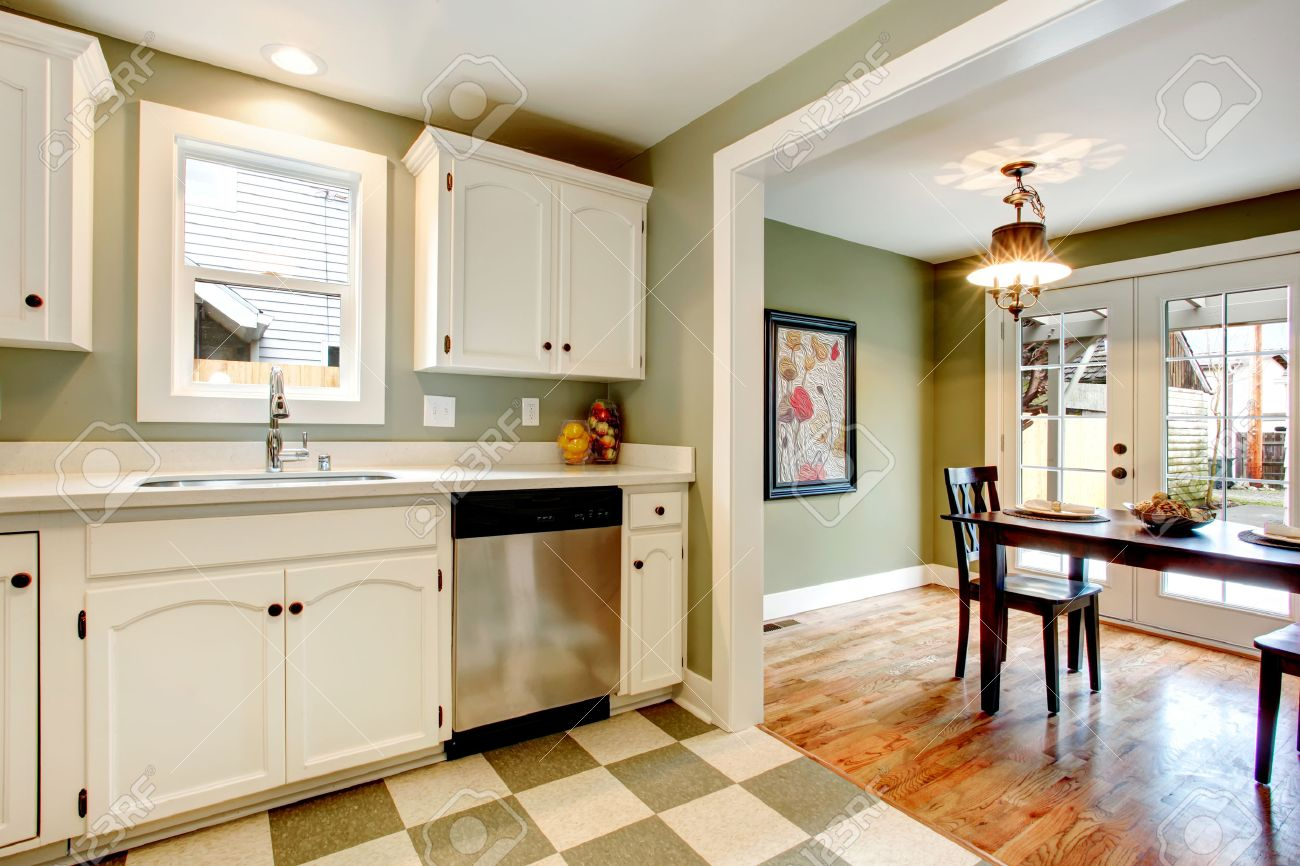 26450812 White kitchen cabinets blends perfectly with light olive walls olive and beige ceramic tile floor Vi Stock Photo
