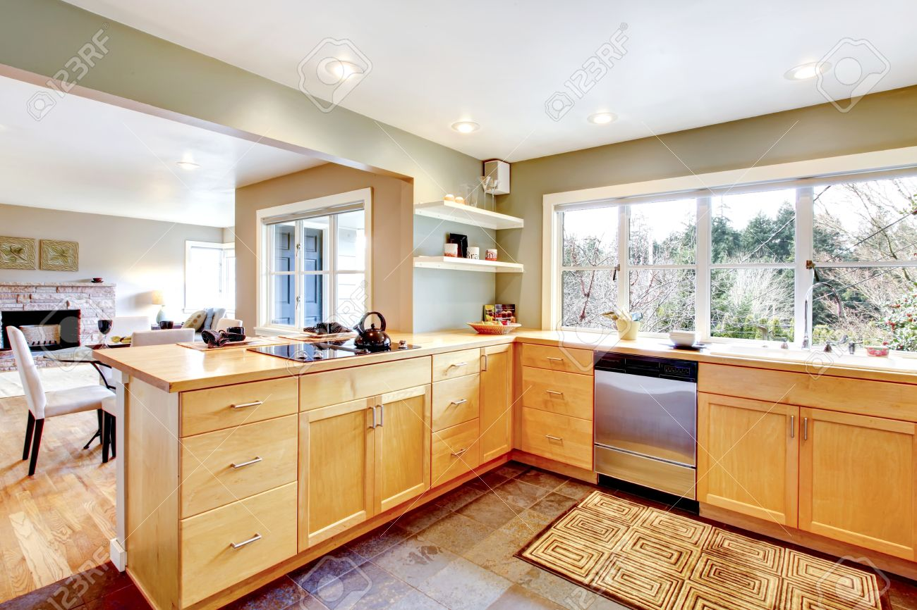 26451079 Kitchen with concrete floor and french window Maple cabinets blend perfectly with light green wall V Stock Photo