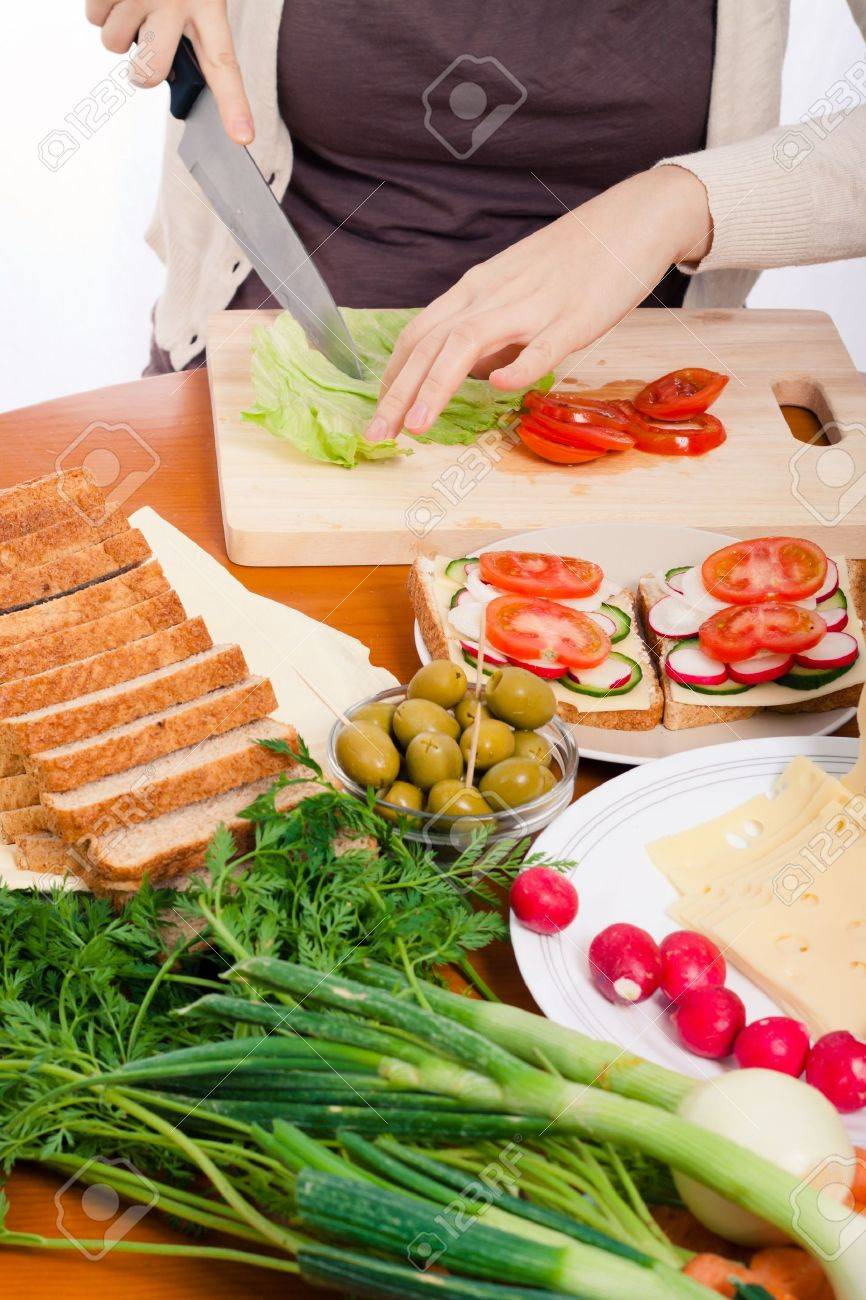 13222739 Detail of kitchen table and woman cutting fresh vegetable and making sandwiches  Stock Photo