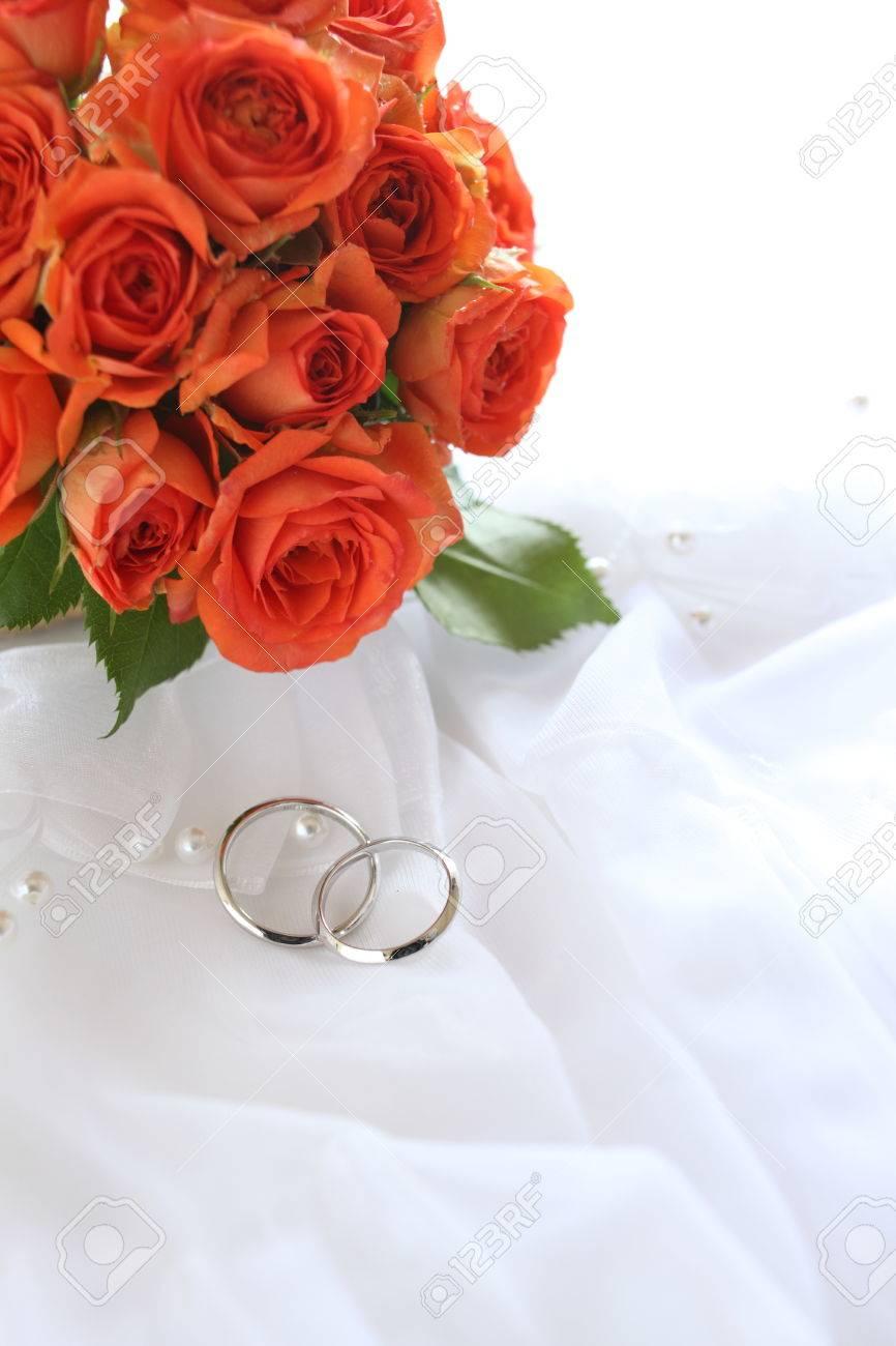 photo wedding bouquet orange roses and wedding rings orange wedding rings Stock Photo Wedding bouquet orange roses and wedding rings