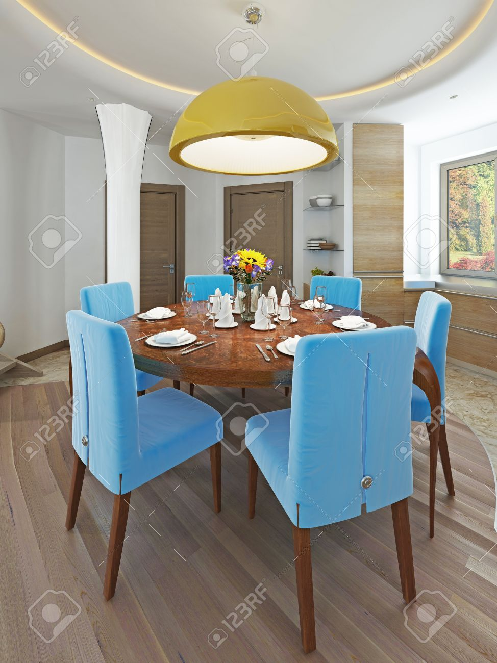 60565125 Modern dining room with kitchen in a trendy style kitsch Round dining table with comfortable blue ch Stock Photo