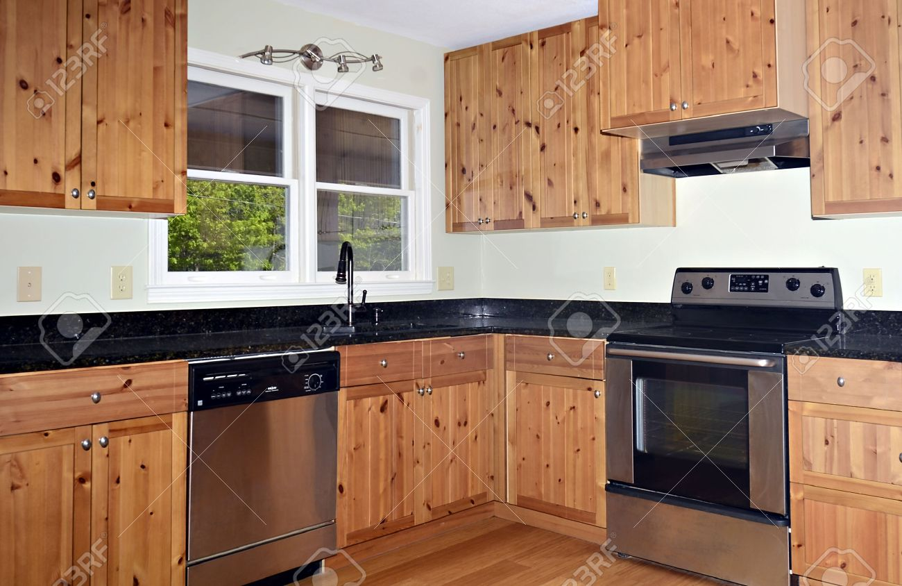 28621950 A small kitchen area with knotty pine cabinets and Bamboo floors Stock Photo