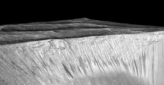 Rastros de agua en el borde de un cráter marciano. Cada una de las líneas oscuras muestra un camino por donde corrió agua, y tienen cientos de metros de alto. Vía NASA JPL/Universidad de Arizona.