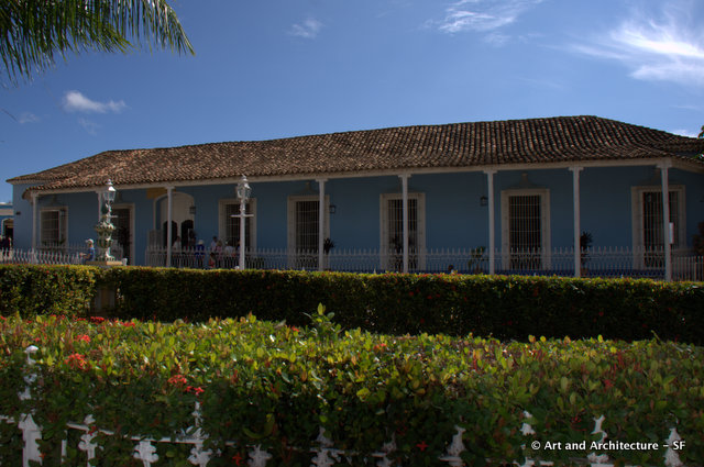 is the House of the Sánchez Iznaga  which houses the Museum of Colonial Architecture This building was originally two houses in the 18th century, both owned by the sugar barons of the Sánchez Iznaga family The two houses, joined in the 19th century show the typical grilled and shuttered windows, and feature an elegant portico with slim columns and a delicate wrought iron balustrade,