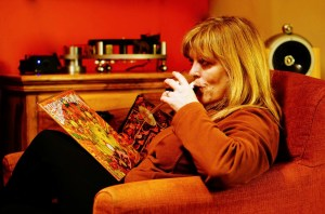 Linda enjoying the luxury of a comfy chair and a house full of records