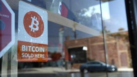A bitcoin sticker is seen in the window of Locali Conscious Convenience store, where one of Southern California's first two bitcoin-to-cash ATMs began operating today, in Venice
