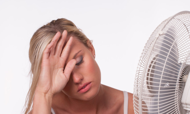 A young woman sits in front of a fan to cool off in a heatwave.