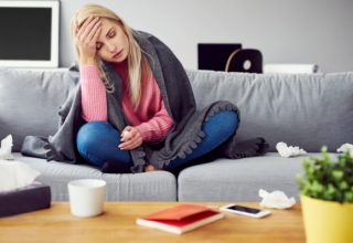 Sick woman with headache sitting under the blanket in living room