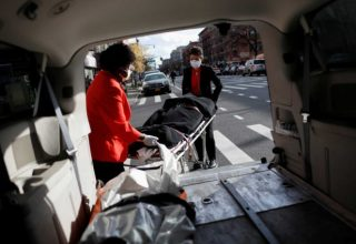 "Nicole Warring, 33, and Lily Sage Weinrieb, 25, both of whom are Resident Funeral Directors at International Funeral & Cremation Services, a funeral home in Harlem, remove a deceased person from a funeral service vehicle, during the coronavirus disease (COVID-19) outbreak, in Manhattan, New York City, New York, U.S., April 16, 2020. REUTERS/Andrew Kelly     SEARCH ""CORONAVIRUS FUNERAL HOMES SLUM"" FOR THIS STORY. SEARCH ""WIDER IMAGE"" FOR ALL STORIES."