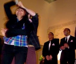 Una mujer bailando y dos hombres esperando que los saquen a bailar.