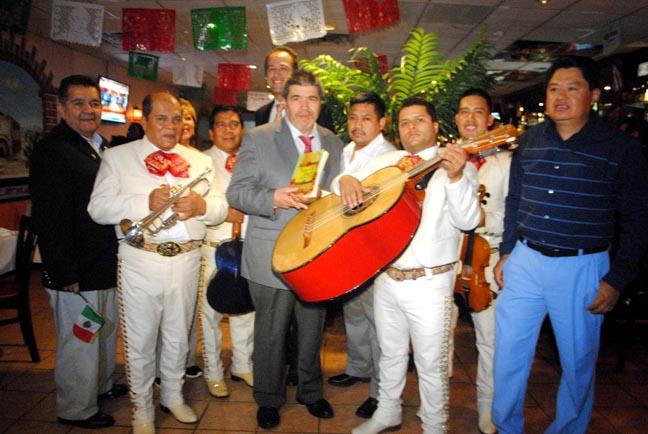 El autor Carlos Velásquez, al centro, con el dueño del restaurante