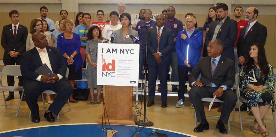 La comisionada Nisha Agarwal hablando y rodeada de representantes de la ciudad e inmigrantes.