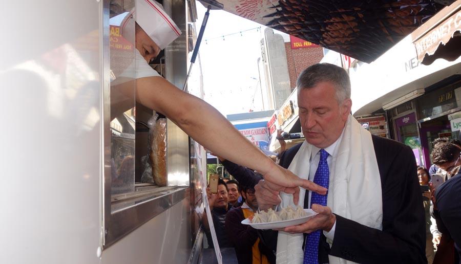 El alcalde Bill de Blasio comiendo Dumplings en Diversity Plaza, Queens.