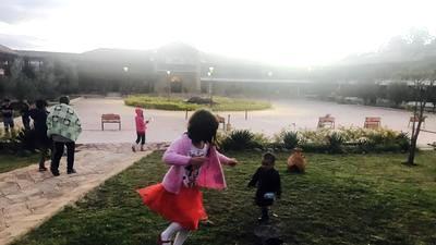 Niños corretean por los jardines de Ciudad de Dios.