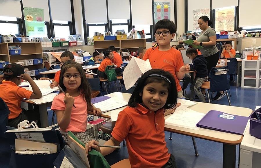 Las niñas Sofía Tapia y Hiydee Chacho en una clase de idioma dual con la profesora Jackie Núñez al fondo.