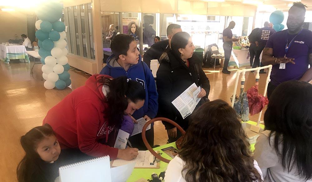 Silvia Rojas en la mesa con información sobre cómo controlar el asma y en compañía de su hijo Luis Hernández y su hija Natali Hernández, al extremo izquierdo.