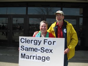 couple demonstrating as clergy for same sex marriage