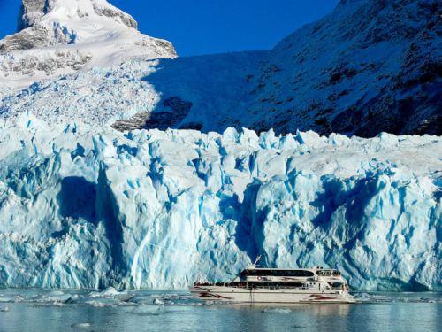 Barco navegando junto al glaciar Perito Moreno en Parque Nacional Los Glaciares de Argentina