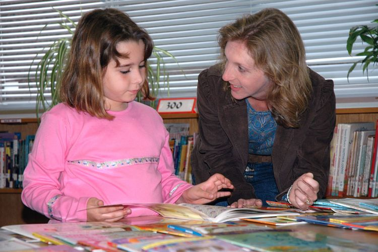 Teacher Helping a Child to Read with Encouragement - via Quick Me Ups