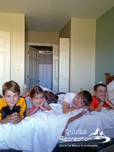 four children resting on a hotel bed