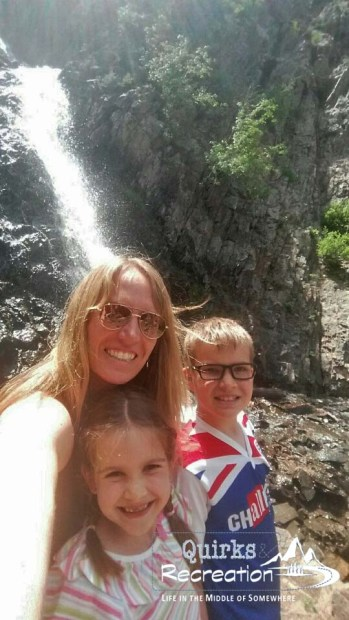 a mom and two children at a waterfall