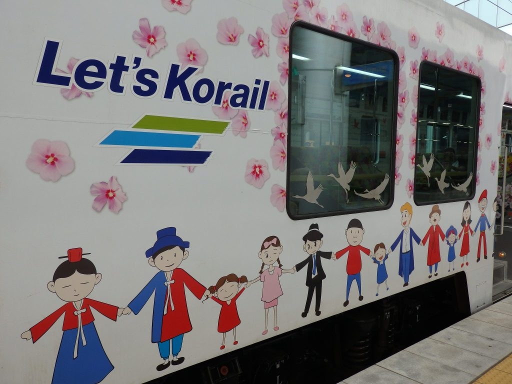 The painting on the side of the DMZ train shows Korean cartoon figures smiling and holding hands.
