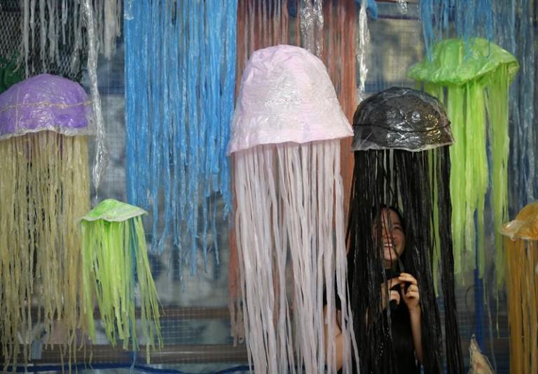 """Una mujer juega con una de las obras de la exposición """"Heart for the Ocean: Break Free from Plastic"""".EFE/Narong Sangnak"""