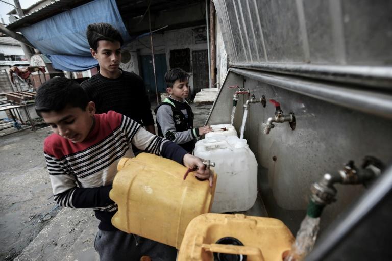 Varios palestinos llenan bidones de agua potable el 22 de febrero de 2017 en Rafah, Franja de Gaza AFP/Archivos / Said Khati