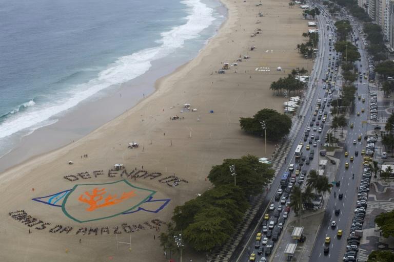 Un grupo de personas, bajo las órdenes del artista estadounidense John Quigley, forman un gran mosaico humano en la playa carioca de Copacabana, contra proyectos petroleros en la desembocadura del río Amazonas, el 29 de marzo de 2017  AFP / Mauro Pimentel