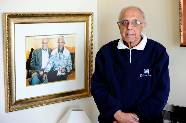 El activista antiapartheid Ahmed Kathrada, compañero de celda del expresidente sudafricano Nelson Mandela, posa junto a una fotografía de ambos el 16 de julio de 2012 en su casa en Johannesburgo AFP/Archivos / Stephane de Sakutin