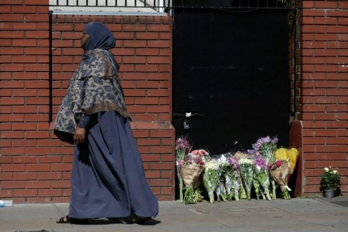 Una mujer pasa al lado de un tributo en el exterior de una mezquita de Finsbury Park, en el norte de Londres, el 19 de junio de 2017, cerca de donde un vehículo atropelló a varias personas la noche anterior   AFP / Daniel Leal Olivas