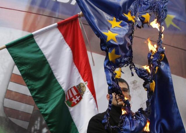 Elod Novak, parliamentary member of Hungarian far-right party Jobbik, burns an EU flag during a demonstration against the European Union, in Budapest