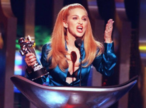"""NEW YORK, NY - SEPTEMBER 8: Madonna blows the crowd a kiss after receiving the award for Best Female Video 07 September during the 1995 MTV Video Music Awards held at Radio City Music Hall in New York. The award was for her """"Take A Bow"""" video. AFP PHOTO (Photo credit should read DON EMMERT/AFP/Getty Images)"""