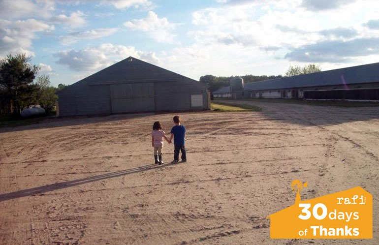 Craig Watts's young children stand outside a poultry house.