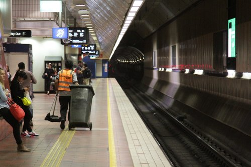 Cleaner does the rounds of Melbourne Central looking for litter, since rubbish bins are no longer provided