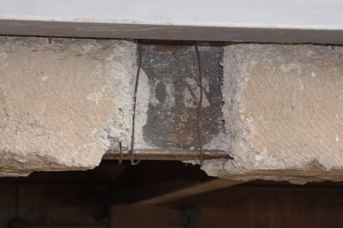 Cracked concrete exposes the internal steel beam along the exterior of the southern side