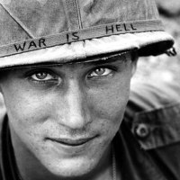 """An American soldier wears a hand lettered """"War Is Hell"""" slogan on his helmet, Vietnam, 1965"""