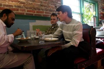 Ewan Robinson, Hal Fischer, and Ashwini Chhatre enjoy lunch at the Red Herring vegetarian restaurant.