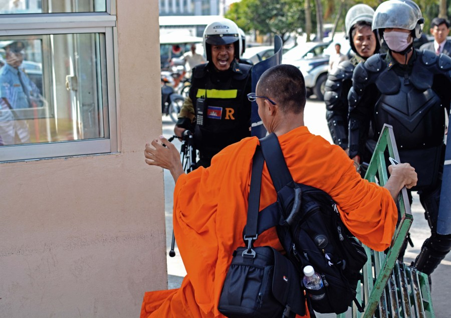A police officer, after confiscating a tripod, yells at a monk protesting in support of Beehive Radio and its director Mam Sonando. // Alex Consiglio
